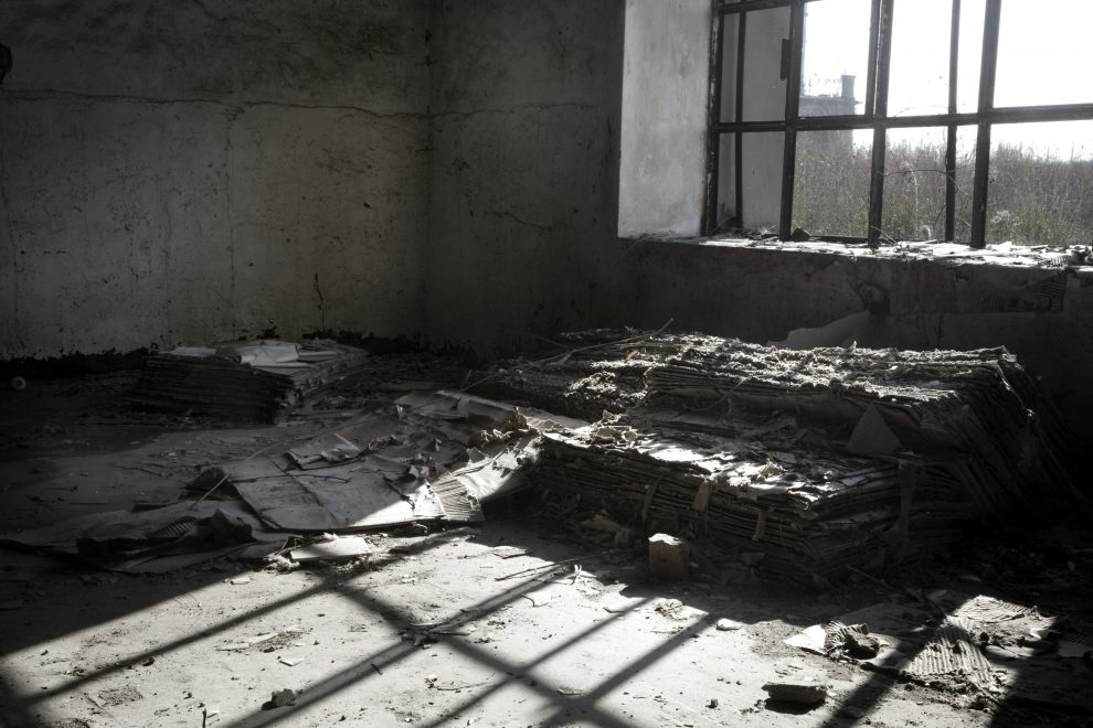 the play of light, inside a dirty room of an old factory in Italy.